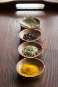 picture of bay leaf  - Dry herb served in wooden plate rosemary bay leaf black pepper turmeric - JPG