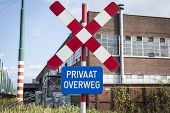image of railroad-sign  - Railroad warning crossing sign in the port of Antwerp - JPG