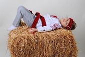 pic of haystack  - Ukrainian girl in national dress and blue jeans lying on a haystack and laughs - JPG