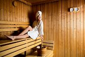 stock photo of sauna woman  - Young woman relaxing on the bench in the sauna - JPG