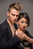 pic of tuxedo  - Young fashionable couple in tuxedos posing in the studio on dark background - JPG