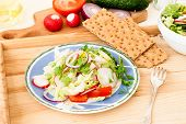 pic of chinese parsley  - Spring salad with radishes cucumber Chinese cabbage and red onion closeup in glass bowl on a white wooden background - JPG