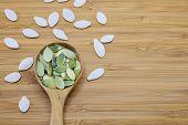 picture of edible  - Edible pumpkin seeds in wood spoon on wood background - JPG