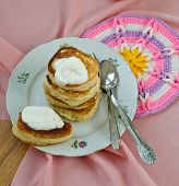 stock photo of frizzle  - Delicious homemade pancakes with sour cream on a pink background - JPG