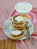 foto of frizzle  - Delicious homemade pancakes with sour cream on a pink background - JPG