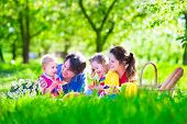 stock photo of little young child children girl toddler  - Young family with kids having picnic outdoors - JPG