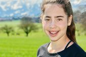 pic of snow capped mountains  - 14 year old Israeli teenager girl in the Switzerland country with green fields and snow - JPG