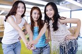 stock photo of joining hands  - Three young female students standing in the classroom and joining hands together - JPG