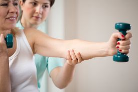 stock photo of physiotherapist  - Woman exercising with dumbbells insured by physiotherapist - JPG