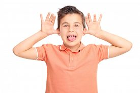 stock photo of sticking out tongue  - Little male kid making a face and sticking his tongue out isolated on white background - JPG