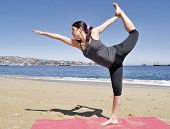 stock photo of dhanurasana  - Yoga teacher practising at the beach pose dandayamana dhanurasana - JPG