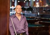 stock photo of hustler  - Confident handsome man with pool stick at billiards nightclub - JPG