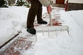 stock photo of cleaning house  - Man shoveling snow at a footpath in front of a house - JPG