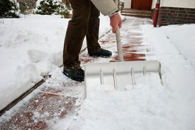 stock photo of house cleaning  - Man shoveling snow at a footpath in front of a house - JPG
