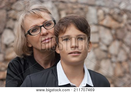 poster of Good-looking single-parent mom and teen son in the park. Photo close up and copy space. Cohesion friendship and family relations.