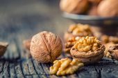 Walnut. Walnut Kernels And Whole Walnuts On Rustic Old Oak Table poster
