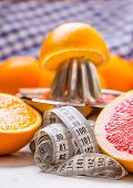 Measure Tape And Juicer With Citrus Fruits. Preparation Of Orange Grape Or Multivitamin Juice, Hands poster