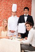 A couple being served by a waiter and a chef in a restaurant