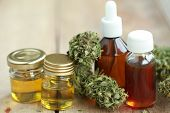 Alternative Medicine Green Leaves Of Medicinal Cannabis With Extract Oil On A Wooden Table poster