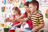 stock photo of child development  - Children painting with teacher in art class - JPG