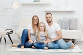 Family portrait. Happy family sitting on floor at home, smiling. Family with one child. poster