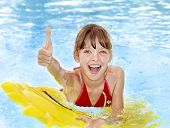 picture of one piece swimsuit  - Children sitting on inflatable ring in swimming pool - JPG