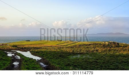 poster of Dirt Road And Green Fields On The Coast, Coastline And Islands With Mountains In A Distance, Moody B