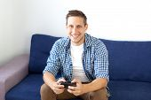 The Concept Of The Game. The Guy Is Playing A Video Game With A Joystick At Home. A Smiling Man In A poster