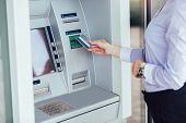 Business Woman Using Atm. Person Using Credit Card To Withdrawing Money From Atm Machine. poster
