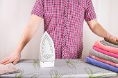 Man Ironing Shirt On Ironing Board. Steaming Iron. Clothes Ironing Board Household Concept poster