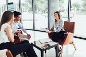 Financial Advisor Showing Report To Young Couple For Their Investment. Salesman And Positive Couple  poster
