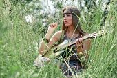 Beautiful Hippie Girl With Guitar Sitting On Forest Glade. poster