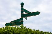 Green Road Sign On The Crossroads With Blue Cloudy Sky And Green Grass In The Background. Traveling  poster