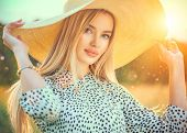 Beautiful model girl posing on a field, enjoying nature outdoors in wide brimmed straw hat. Beauty b poster
