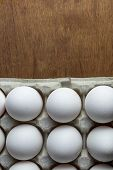 Chicken Eggs Are Raw In The Tray. The Shell Is White In Eggs. In One Section Is An Egg Shell. On One poster