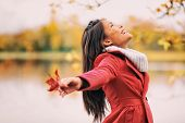 Autumn woman happy smiling feeling free in fall nature. Nature people beauty landscape. Girl by the  poster