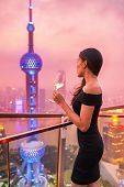 Luxury lifestyle Shanghai city Asian woman drinking white wine glass at rooftop bar party night rich poster