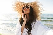 Photo of joyful brunette woman in beach dress and straw hat smiling while walking by seaside in summ poster