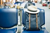 Blue Vintage Bag Or Hipster Backpack With Hat On Seat At The Interior Of Airport Terminal. Travel Co poster