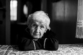 Black and white portrait of a lonely sad old woman. poster