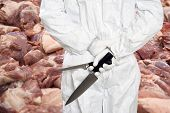 stock photo of slaughterhouse  - Butcher standing in front of a large stack of raw meat  - JPG