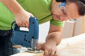 image of workbench  - Man working wood with electric saw ans safety goggles - JPG