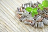 stock photo of mints  - herbal capsules with mint leaves on straw pad - JPG