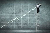 foto of staircases  - businessman standing on ladder drawing diagrams and graphs - JPG
