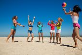 Group of young joyful girls playing volleyball, passing the ball to each other on the beach