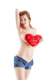 stock photo of lewd  - Sexy topless Caucasian woman covers her breast by holding heart shaped pillow that had writing on it  - JPG
