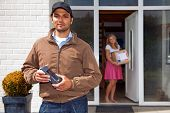 Delivery guy, holding a wireless pin machine walking away from a house, where a woman stands in the