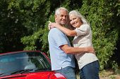Smiling mature couple hugging against their red cabriolet on a sunny day