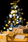 pic of gift wrapped  - Christmas gift gold ribbon with a christmas tree in the background - JPG