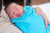 stock photo of bassinet  - Newborn Asian baby girl fall asleep in mother - JPG